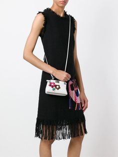 White nappa leather micro 'Peekaboo' crossbody bag from Fendi featuring a trapeze body. a detachable and adjustable shoulder strap and silver-tone hardware and a multicoloured floral appliqué detailing. Fendi, Gucci, Bago, Ysl, Givenchy, Versace, Burberry, Chloe, Prada