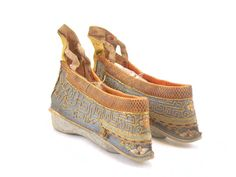 Chinese foot-bound shoe, with a light blue silk background along the sides and a gold silk ankle guard. It is decorated with a pink and blue chequered galloon, a Greek key pattern and floral motifs. The more ornate and skilfully sewn the boot, the more highly regarded the wearer, who would have sewed them herself. The wearer's foot would have been approximately 4 inches meaning she would have been known as a 'silver lotus'. Date: 1700-1914 #shoes #fashion