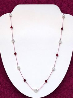 Floating Garnet and Pearl Necklace  by Michele Rose  Learn to create a beautiful knotted piece of jewelry with Swarovski pearls and crystals on exposed silk cord. This floating bead necklace technique is a fun, easy and inexpensive piece to make. Perfect for January or June birthdays, this casual and sweet necklace style was made popular by the movie Tin Cup.