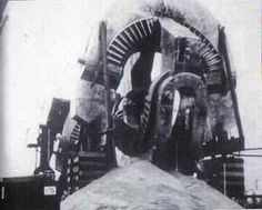 """This massive piece of machinery was one of six excavated around 1990 from a great depth on secret government property in the United States, then promptly reburied in the same area. The enormous device dwarfs the dumpster and the crane shown to its left. Nobody has been able to definitively identify this mind-boggling machinery. This photo is from a book titled, """"The Rainbow Conspiracy"""" by Brad Steiger and Sherry Hansen Steiger."""