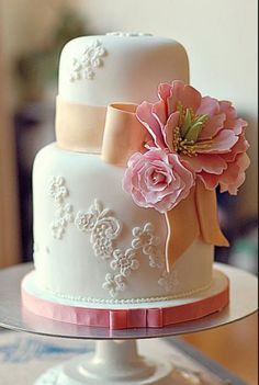 2 tier small mini wedding cake in white with pink ribbon and pink flower and orange bow.