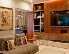 Outra sala de tv com lareira embutida sob o móvel. Vale lembrar que esta solução só funciona com lareiras elétricas ou a gás para não danificar os equipamentos. Projeto Zize Zink, via Arkpad.