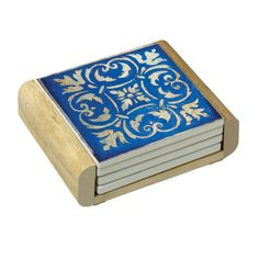 """Add a touch of the mediterranean to your coffee table with this beautiful set of coasters! Crafted from natural stoneware that absorbs  drips and  condensation and a durable cork bottom to protect your  tabletops.  The  beautiful blue tile design is inked onto the stone.   The  coasters are housed in a wood  holder for easy storage and organization.  Set of 4 including 4 stone coasters and a wood holder. 4"""" coasters.  Made in the USA."""