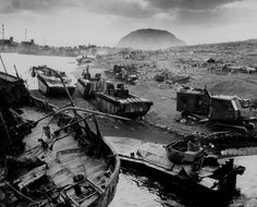 """Across the litter on Iwo Jima's black sands, Marines of the 4th Division shell Jap positions cleverly concealed back from the beaches. Here, a gun pumps a stream of shells into Jap positions inland on the tiny volcanic island."""" Ca. February 1945."""