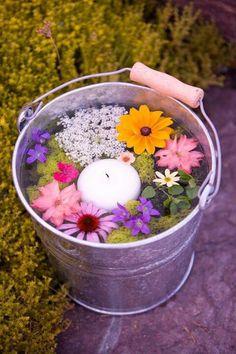Dit ziet er feestelijk uit. Vul een emmer met water, verse bloemen en druifkaarsen.