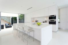 All-white modern kitchen with large long island with bar stools