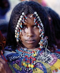 Africa | An Afar girl has her attractive hairstyle embellished with buttons and beads, which is typical of the young girls of her tribe. Proud and fiercely independent, the nomadic Afar people live in the low-lying deserts of Eastern Ethiopia. | © John Warburton Lee