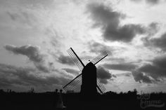 Silhouetted against the cloudy sky. October wedding, couple in front of the Windmill at Avoncroft Museum of Historic Buildings (avoncroft.org.uk). Black and white photograph. Jay Emme Photography.