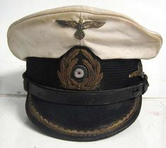 Reproduction German U-Boat Submarine Captains Peaked cap with 70+ years of ageing and numerous light oil stains and some lightly worn and tarnished areas as worn by the Captain of U-96 Heinrich Lehmann-Willenbrock.  The peak, liner and chinstrap etc. all show good wear and both the inside and outside are stained and aged. Notice the gold emblem and Captains peak ranking are dark and tarnished. Notice the wear, dirt and oil stains particularly on the top of the cap. www.warhats.com