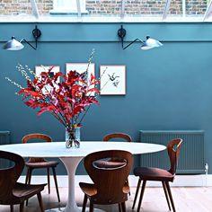 """<p style=""""text-align: justify;"""">C'est dans la véranda qu'Aude a aménagé la salle à manger. Table ovale en marbre inspirée d'Eero Saarinen. Chaises..."""