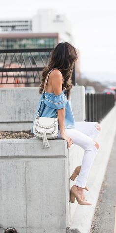justthedesign:  The off the shoulder top trend is one which is coming back with a bang this spring!Christine Andrewwears the look on a beautiful embroidered denim top paired with white jeans - the ultimate spring classic. Top/Jeans: Bloomingdale's, Heels: Intermix.