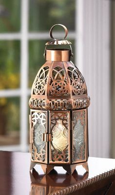 "Candleholders & Candles Home Locomotion Intricate swirls of gleaming copper add luster to this dramatic candle lantern, imparting the feel of a timeless treasure. Unique double-door design is sure to add a faraway flair to any surroundings! Weight 0.6 lb. Iron and glass. Tealight candle not included. 4"" diameter x 9 1/2"" high."