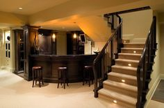 A basement home bar with a curved bar and an opening to the family room beyond. Pendant lights above the bar keep it well lit.