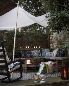 Lag et hyggelig sitteområde med benker, puter, pledd og belysning