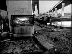 "Magnum Photos.  Jim Goldberg USA. San Francisco. 1991. ""Under Highway 280, San Francisco."" A picture of the Mediterranean in this squat reminds the homeless youth who stay here of ""home."" As San Francisco becomes gentrified with the dot-com boom, the homeless are pushed further and further out of the center. Squats such as this one are taken up by streetkids and homeless adults south of the city."