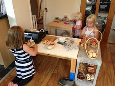"""bakery play - The blogger made reusable """"baked goods"""" from painted and sealed salt dough, provided play dough/baking cups/pretties/cellophane/ribbon for making treats, shopping baskets, and a cash register."""