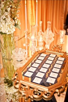 obsessed with this idea for your placecard table... assorted gold frames...From Paris with Love. Escort card display or mirrored table with vintage crystal.