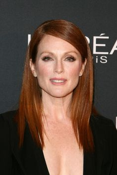 """The 56-year-old redhead told People that """"it's a privilege to age."""" But her deep part and sleek, pin-straight hair (styled with the help of a straightener) help her look timeless."""