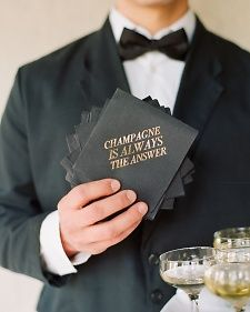 Simple black cocktail napkins printed with a bubbly slogan in gold foil set a festive (but still elegant) tone