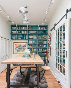 Mesón al centro de la sala de muros blancos y repisa, casi a muro completo, de color calipso. El mesón es de estructura metálica y cubierta de madera, con ruedas en las patas y pisos que se esconden. El taller perfecto para un ilustrador.