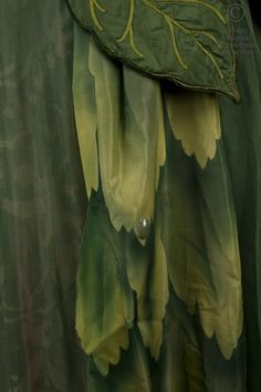 Dance Dress 1954: Une fée. Fantastic costume of medieval style. With Brown faille strapless long dress, trimmed with feathers and leaves in green tulle; sleeves adorned with Ivy and pink flowers. Painted pink and green silk skirt covered with green tulle with panels in silk painted with plant motifs lined iridescent cabochons. Pair of gloves gauntlet green and Brown silk trimmed with green feathers.  Detail