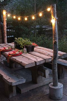 Small logs and cement help create the mood by holding up a string of lights above your picnic table!