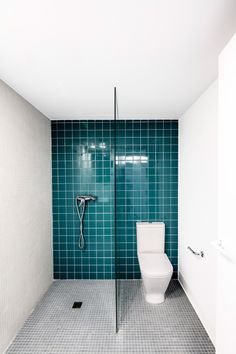 The team inserted a pair of freestanding cubes to this apartment to house these green-tiled bathroom facilities.
