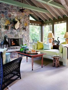 Rustic Chic. Styles collide in this unique, rustic-meets-trendy sunroom. A dramatic stone fireplace surround and furnishings of weathered wood convey down-home comfort. Accents of mint green, such as the painted ceiling beams and upholstered sofa, incorporate of-the-moment style.