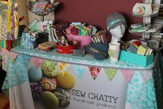 Love the banner. Great little table at a craft show.  I'm almost certain it is an ironing board.  Great idea!! Portable, perfect height and not too wide so it wouldn't take up as much space as a standard width table.