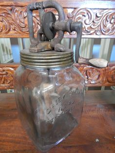 """Large Vintage Style Glass Butter Churn. Functioning Rusted Metal Top. Glass marked """"DAZEY CHURN NO 40 PATENTED FEB 1422 DAZEY CHURN PGCO ST LOUIS MO"""". Dimensions: 13"""" Tall 6"""" x 6"""" Square Bottom"""