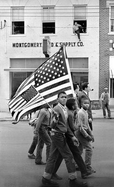 Photo: Stephen Somerstein. 'Young civil rights marchers with American flags march in Montgomery' 1965