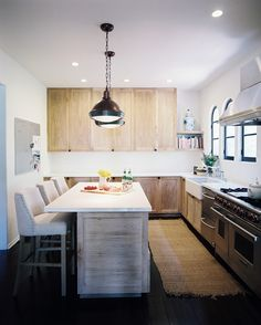 An open kitchen with wood cabinets and white countertops