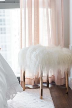 Blogger Jessica Sturdy of Bows & Sequins shares her Chicago Parisian-chic bedroom design. CB2 white shag stool with brass legs, Pier 1 sheer pink linen curtains.