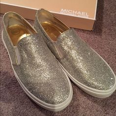 Michael Kors sneakers Silver sneakers with gold trim by Michael Kors. New with tags on bottom. Bottoms are a little dirty since they were the last pair store had in stock and must've been floor model. Never worn since purchased and in perfect condition. Michael Kors Shoes Sneakers