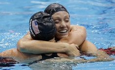 United States' Dana Vollmer embraces United States' Claire Donahue after Vollmer's gold medal win in the he women's 100-meter butterfly swimming final on Sunday, July 29. Click to see more photos. PHOTO BY DANIEL OCHOA DE OLZA / THE ASSOCIATED PRESS