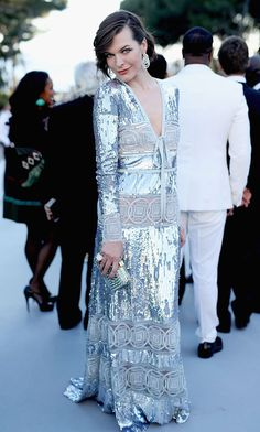 Ambassador of amfAR Milla Jovovich dazzled in a v-neck silver gown featuring sheer panels of circular cutouts.