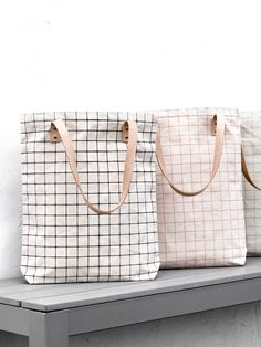 These cotton canvas tote bags by 5mm Paper show a modern graphic grid lines design. The bags are made from strong canvas and have natural tanned light brown straps with golden studs. The bag has a zipper and inside pocket for extra convenience. A minimalist fashion style for a trendy look. #tote #bag #natural #cotton #canvas #leather #straps #zipper #trendy #grid #lines #modern #minimalist #style