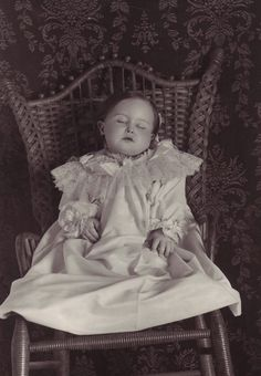 Postmortem photo of a child propped in a chair.
