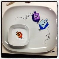 Make the holidays special with this Hanukkah dreidel serving platter. This cheerful  ceramic plate features a festive dreidel pattern that will brighten your table. Your guests will be sure to admire the hand-painted details and craftsmanship. This set includes 1 platter and 1 bowl. Perfect for latke's and applesauce. Please choose 3 colors. 1 for each dreidel. Personalize it at no additional cost.  Retail Price $39.99 www.not2shabbey.com  #Chanukah #gift #Hanukkah #present #latkes #applesauce