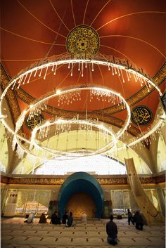 "Prayer hall of Şakirin Mosque in Istanbul, Turkey. The chandelier has large, asymmetrical rings bearing the 99 names of God written in Arabic and waterdrop-shaped glass globes made by Nahide Büyükkaymakçı, ""reflecting a prayer that Allah's light should fall on worshipers like rain""."