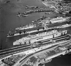 RMS Queen Mary and other vessels in dock, Southampton. An aerial view of RMS Queen Mary. The Queen Mary was in service for Cunard between 1936 and 1967, apart from her war work as a troop ship which ended in September 1946. At the time of this photograph the Queen Mary was being used to repatriate the families of Canadian servicemen.