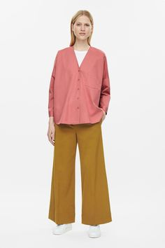 A collarless design, this v-neck shirt is made from cotton poplin with a single patch pocket. An oversized fit, it has exaggerated dropped shoulders, front buttons and neat finishes.