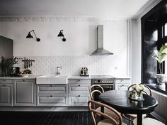 Grey kitchen in a Swedish home with dramatic black accents. Anders Bergstedt for Entrance.