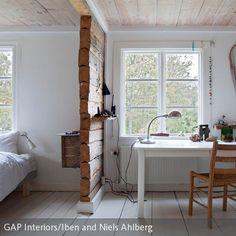 Die Trennwand aus Holz separiert Arbeitsplatz und Schlafbereich in diesem Schlafzimmer. So werden diese Bereiche optisch voneinander getrennt und der …