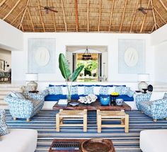 Bohemian living room with blue chairs and rush ottomans, woven ceiling and indoor plant
