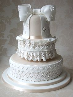 A Vintage Look. Your cake decorator should have no problem doing this. If you are doing it yourself and fell ambitious, use fondant and do cutouts to get a beautiful lace-look. Otherwise, use real lace (just like putting ribbon on), and use whatever very-thick ribbon you want to make the bow on top (using a piece of wire to hook it upright).