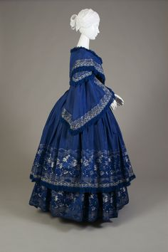 Blue silk taffeta evening dress with two-tier skirt. Antedates Virginia Shields Vaden's marriage to William Vaden in 1858. The bodice is low cut and the sleeves are very long…