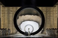 At the Israeli Opera, Tel Aviv-Yafo – IL, 6 to 25 March 2017. A co-production of Tel Aviv Opera, Teatro Regio di Torino, Opéra de Lausanne In Poda's Faust, a huge ring occupies the scene, surrounded by an architectonic box enclosing the stage. The ring, which rotates and takes different inclinations, creates different settings according …