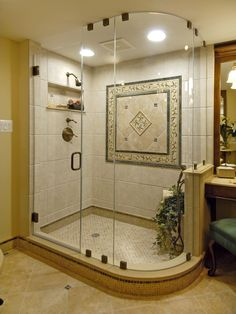 """The """"limestone"""" in this shower is actually a porcelain lookalike that's less expensive and easier to maintain. The medallion is composed of marble, mosaic tile and natural limestone. The splurge here, says designer Carolyn Thomas, is the curved glass chamber and two-way hinged door that keeps water inside… More"""