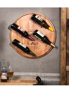 Wine Barrel Wall Wine Rack for $135.00 from WineRacks.com  Dimensions: 21.3 diameter x 4 deep Capacity: 4 bottles  Bring a little of the winery to your wine storage with this wine barrel top that stores 4 special bottles of wine on your wall.